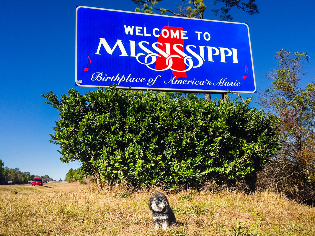 Willie stops on the side of the road at the Mississippi Welcome sign