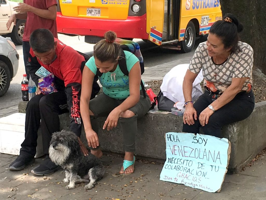 Willie takes a break with some Venezuelans on the streets of Medellin Colombia