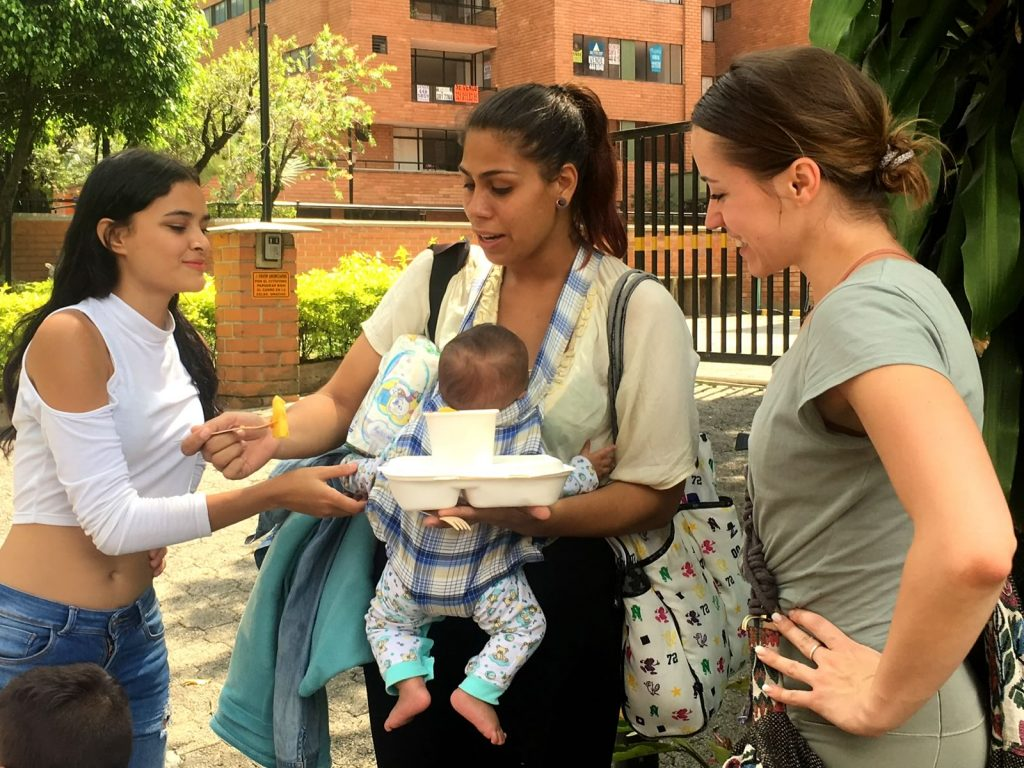 Willie's volunteers Diana and Dasha give food to a Venezuelan mother in Medellin Colombia