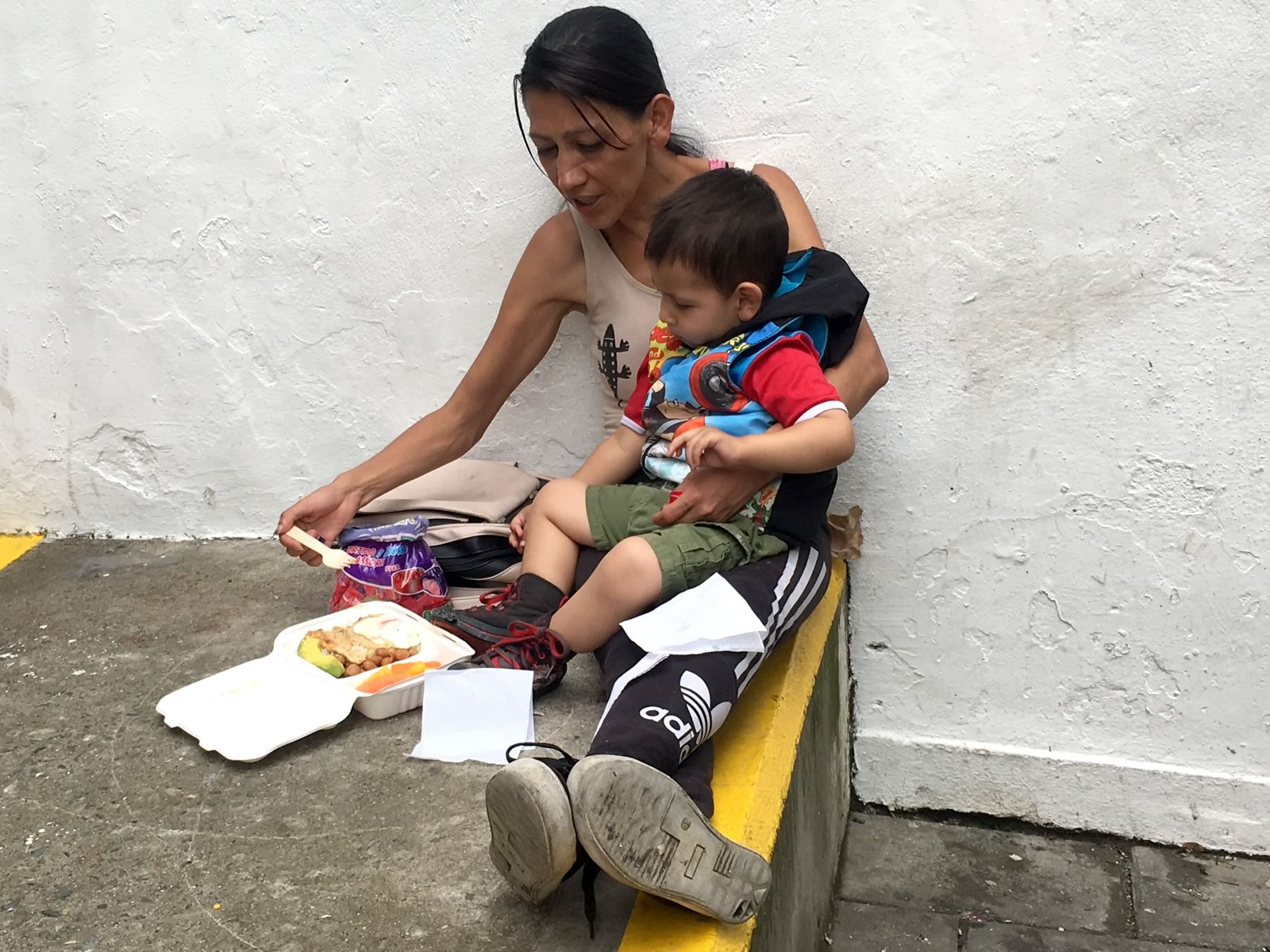 A Venezuelan mother feeds her child a meal provided by the Where is Willie Foundation