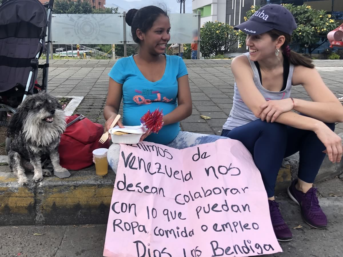 Lorena and Willie take a break to speak with a Venezuelan woman on the streets of Medellin Colombia