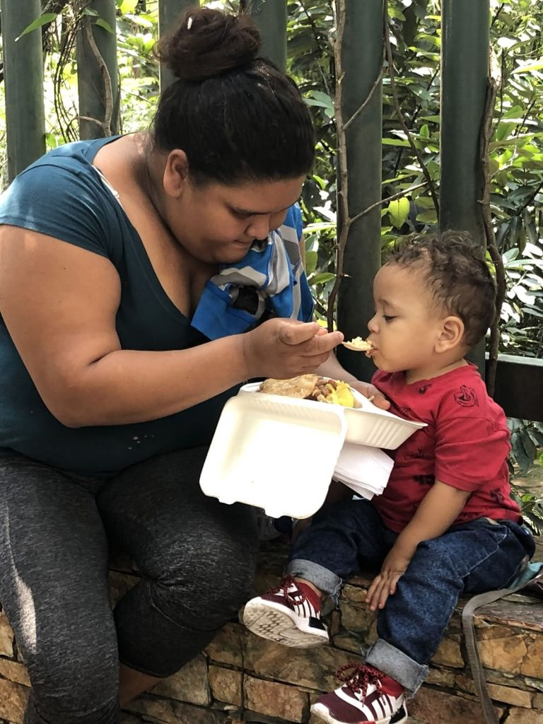 A Venezuelan mother feeds her baby some of a meal provided by the Where is Willie Foundation