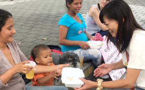 Yoriko gives a meal to a Venezuelan family in Medellin Colombia
