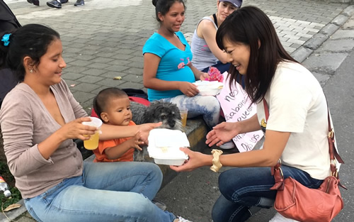 willie watches on as yoriko hands out a meal to a Venezuelan family